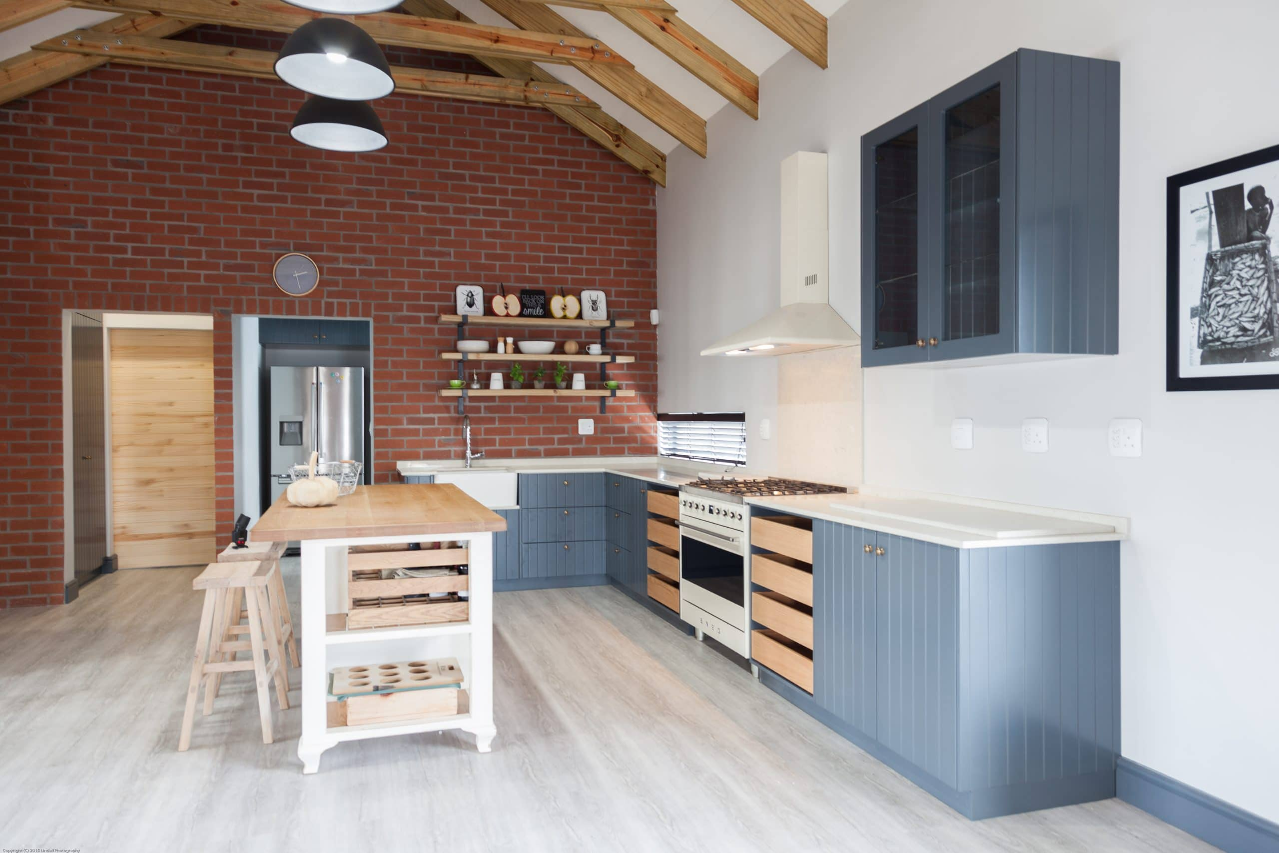 exposed red brick wall kitchen farm style butler sink and open trusses