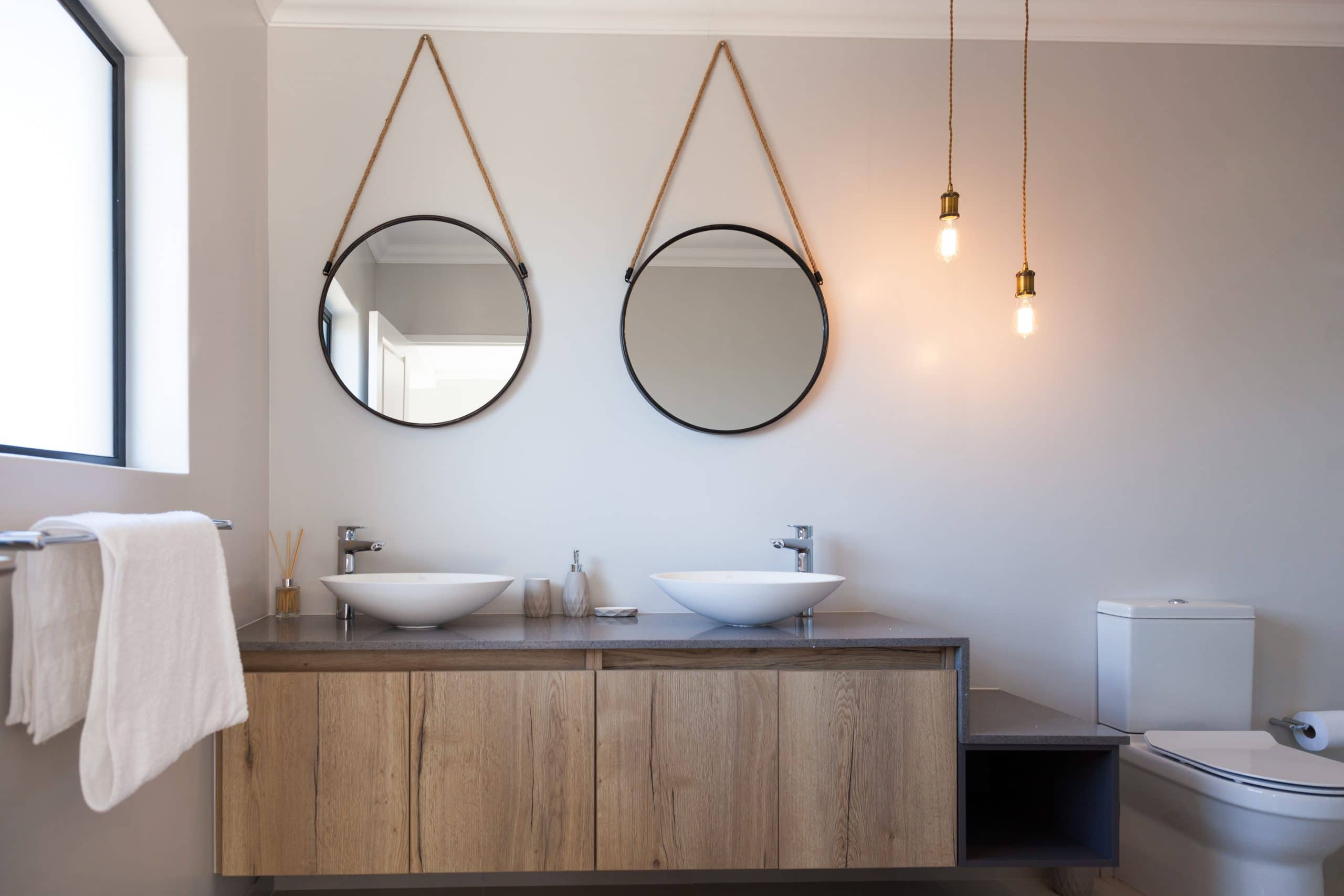 round coricraft hanging mirrors over bathroom vanity with grey quartz tops