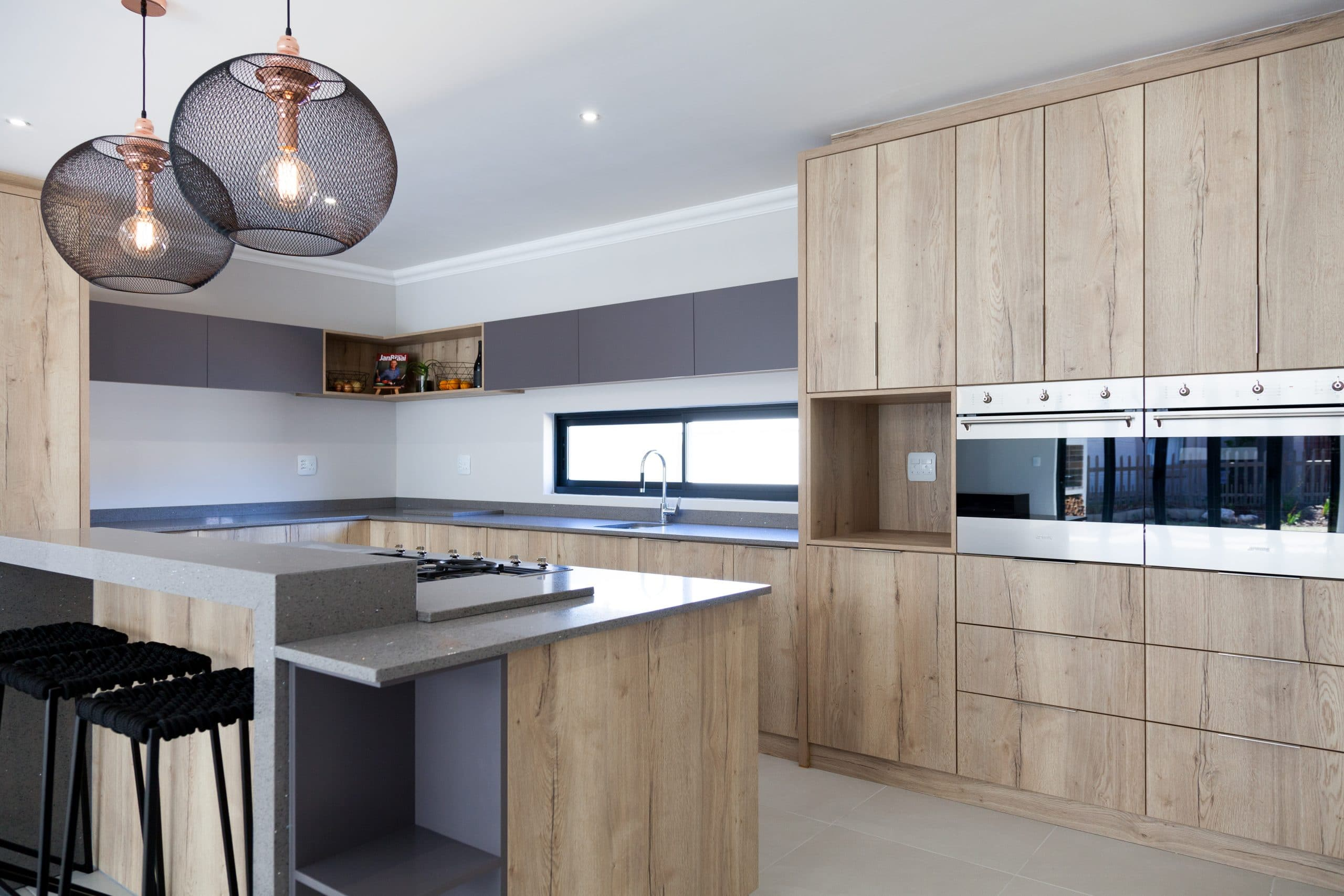 wire pendants with filament bulp lightning over kitchen island with smeg appliances