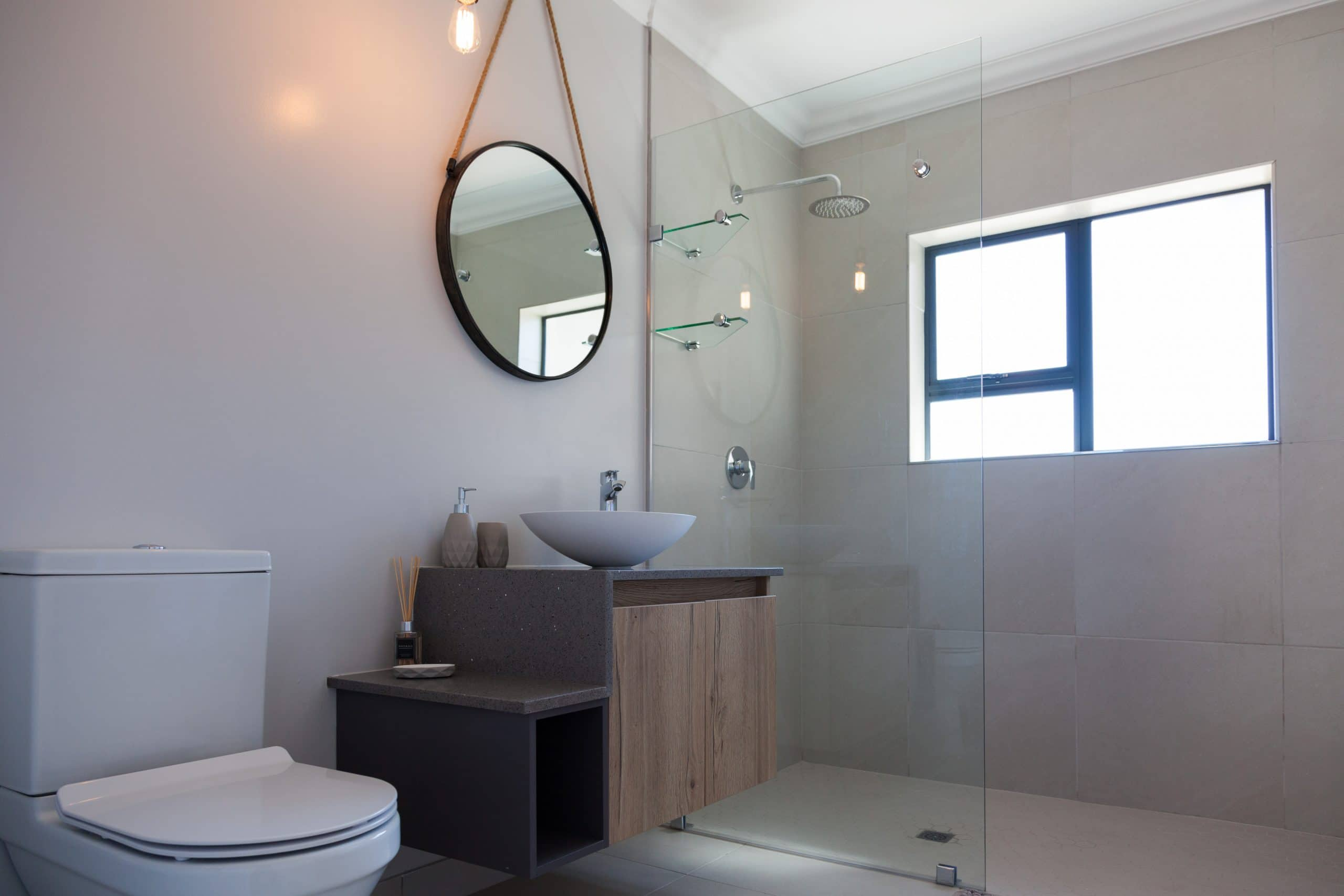modern vanity design with round mirror and frame less shower panels