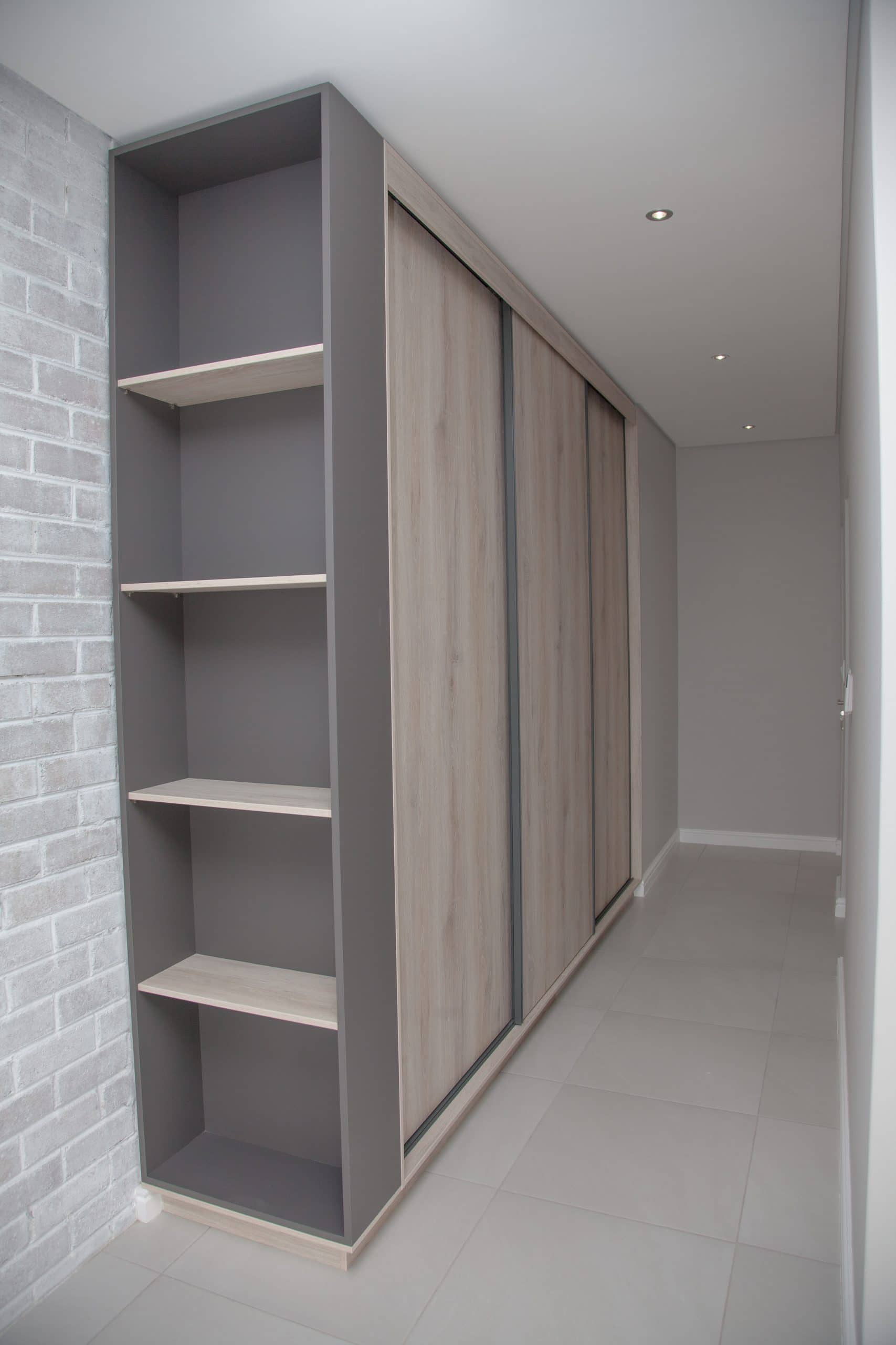 sliding bedroom cupboards with exposed white washed brick