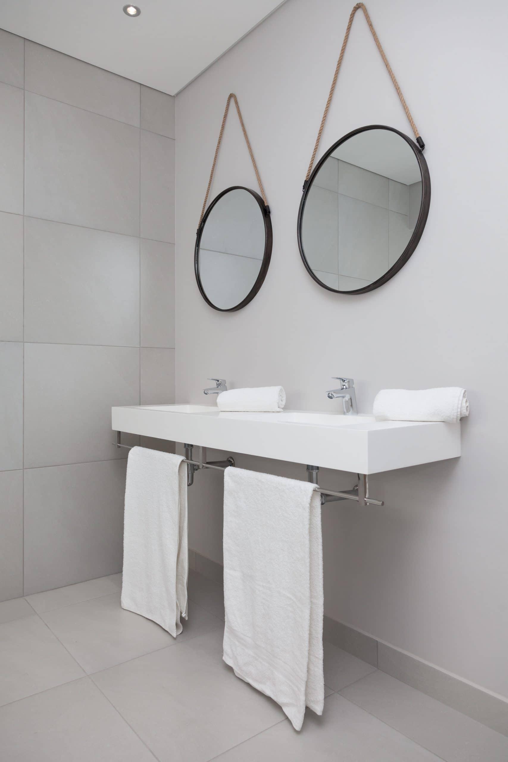 round coricraft hanging mirrors over custom wall hung basin