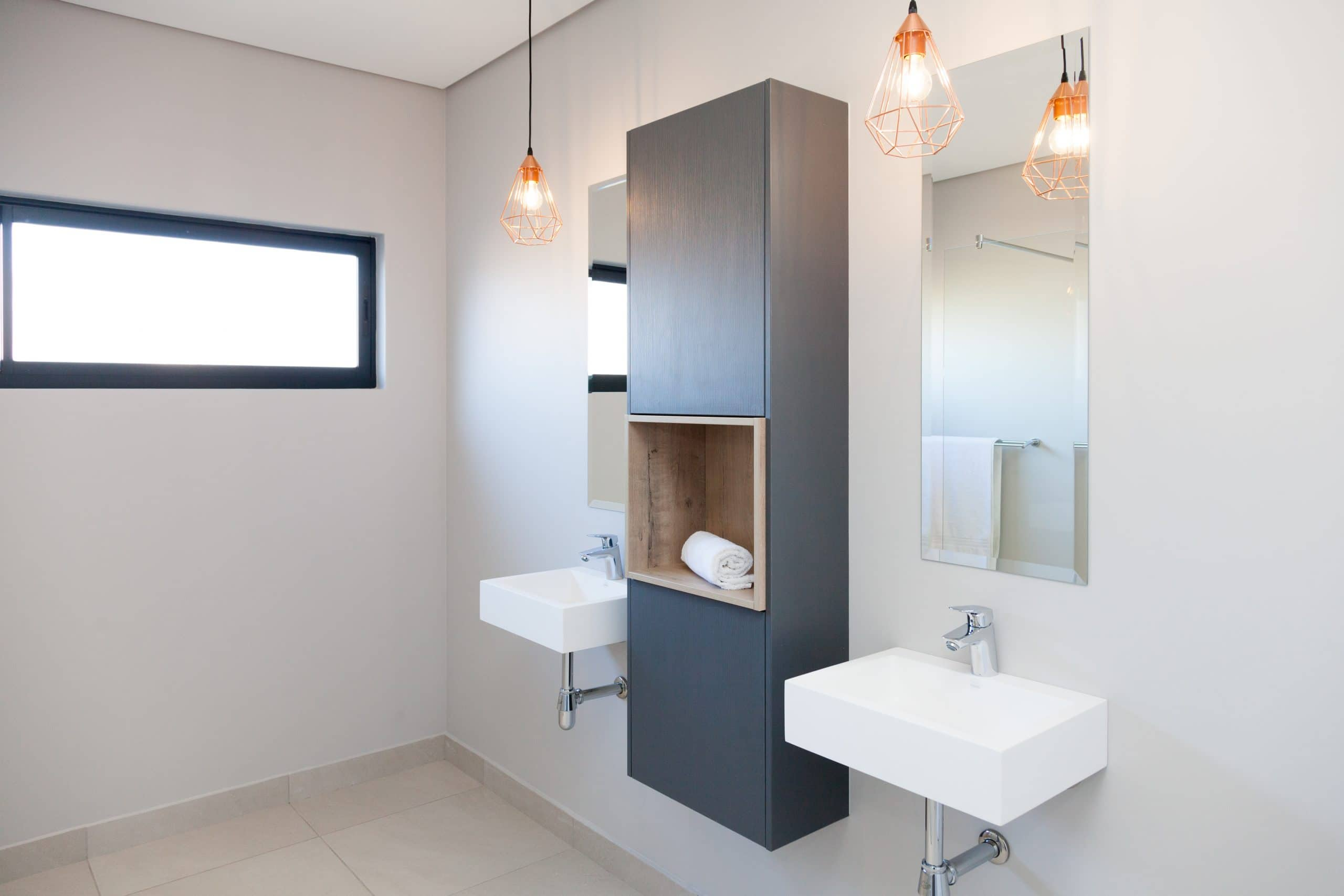 wall hung basins with side dark grey cupboards and handing pendants bathroom