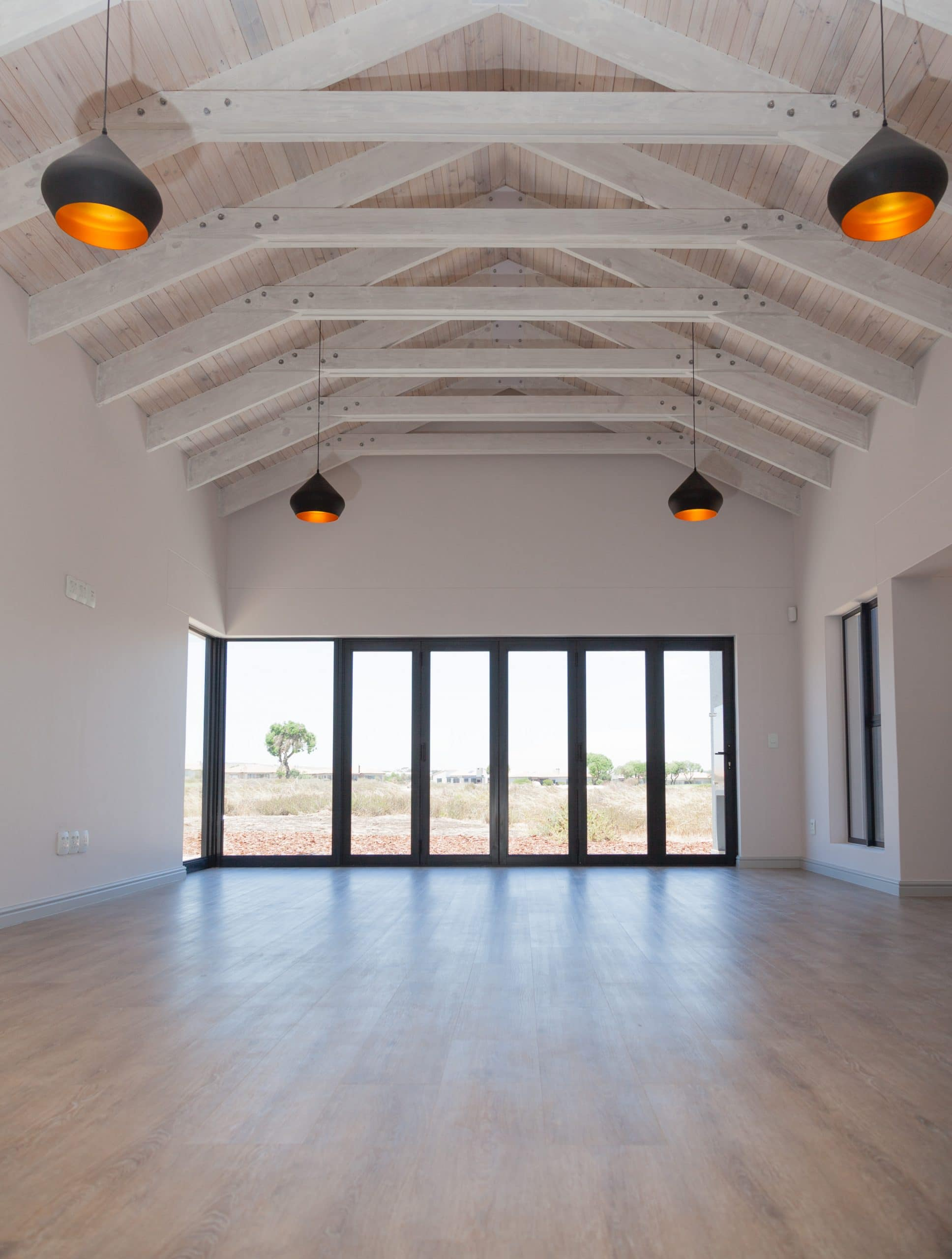 black pendants handing from wooden exposed trusses white washed overlooking langebaan country estate