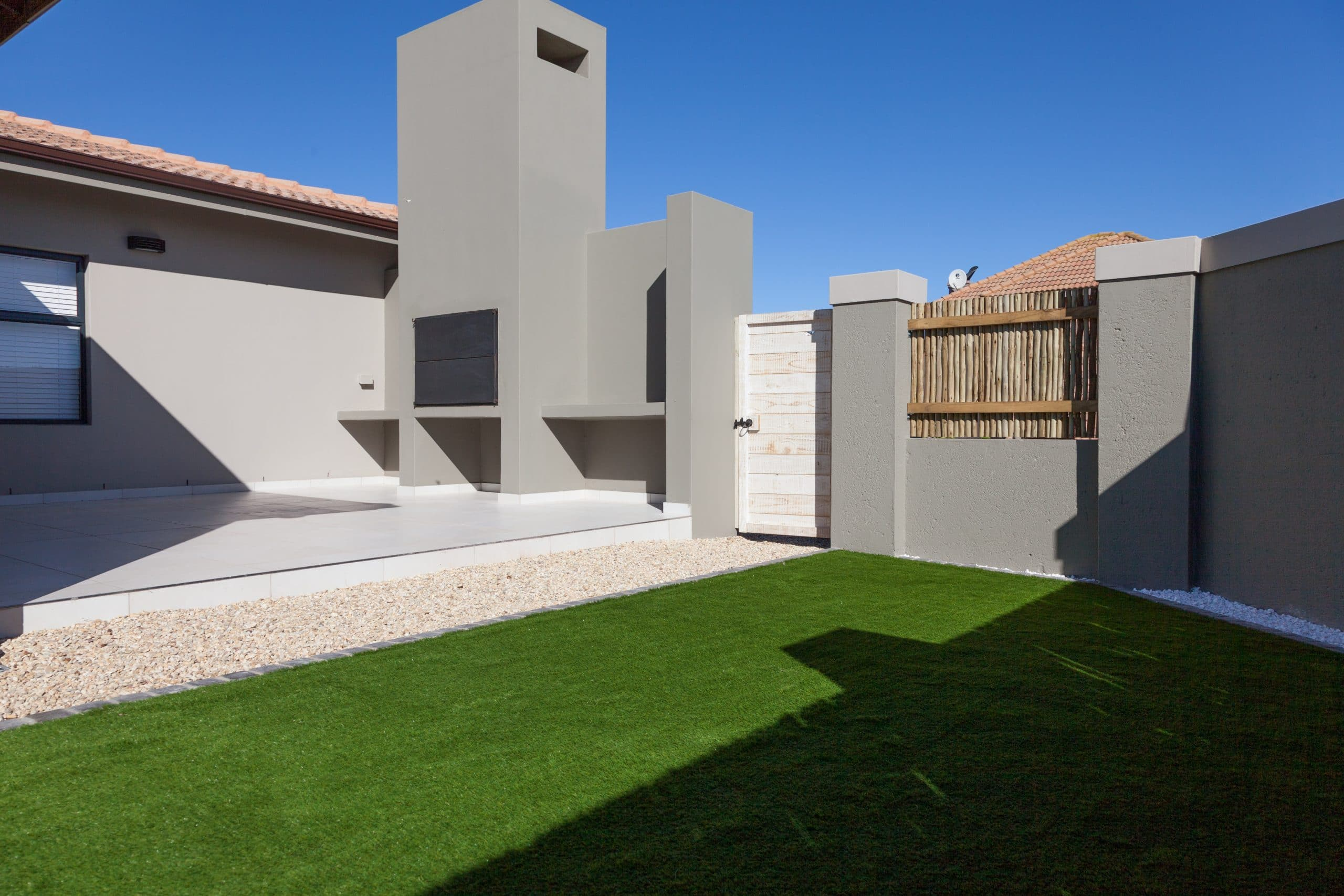 artificial lawn with white washed wooden gate in estate
