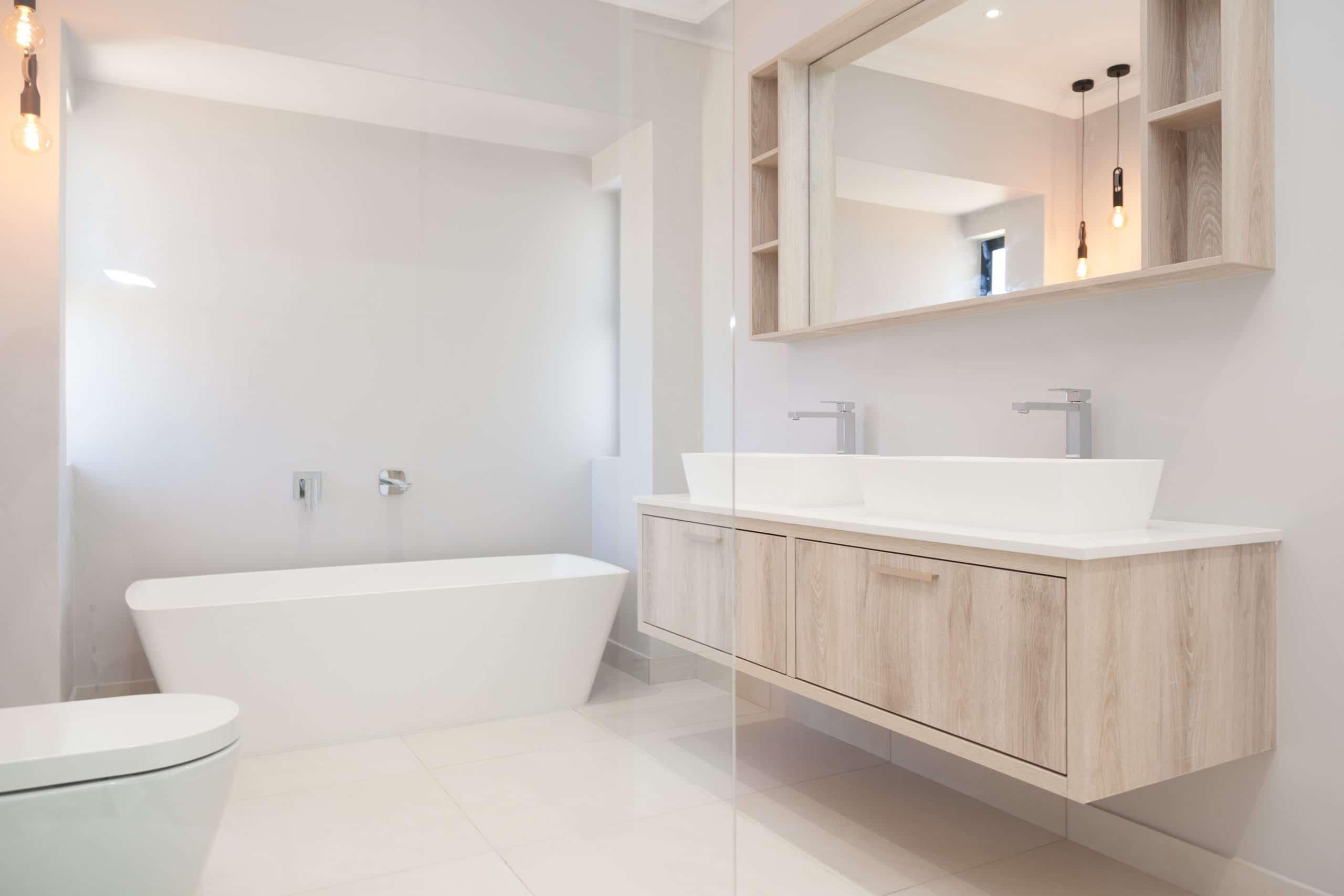 modern light bathroom with freestanding bath hanging pendants wooden vanity