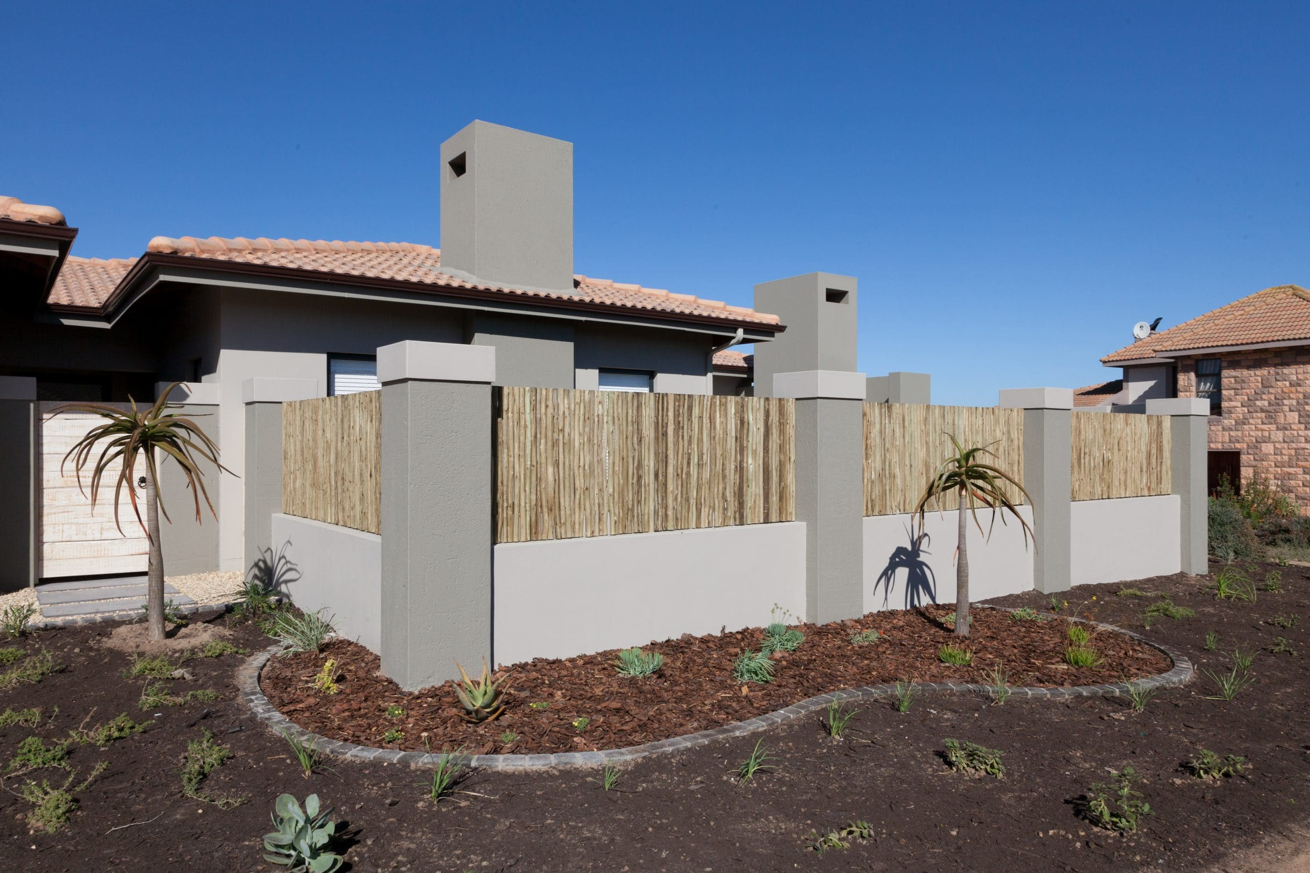 wattle fence on top of low brick and plastered wall landscaped area langebaan country estate