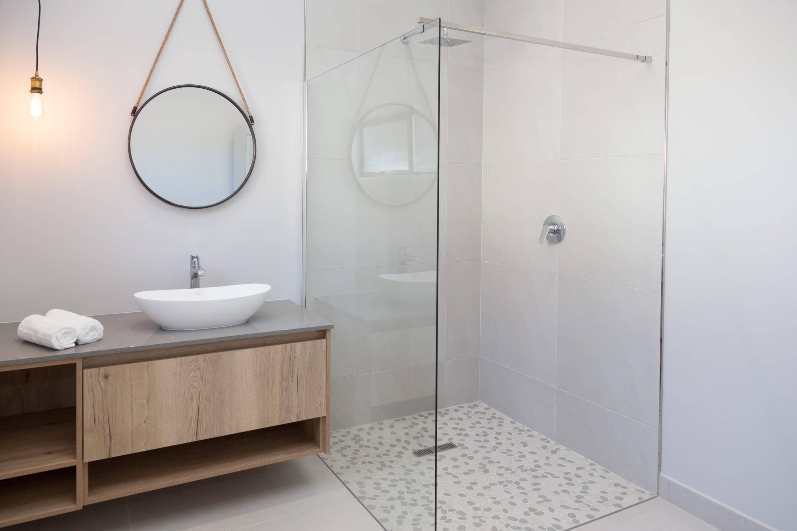 open shower with round coricraft hanging mirror bathroom vanity