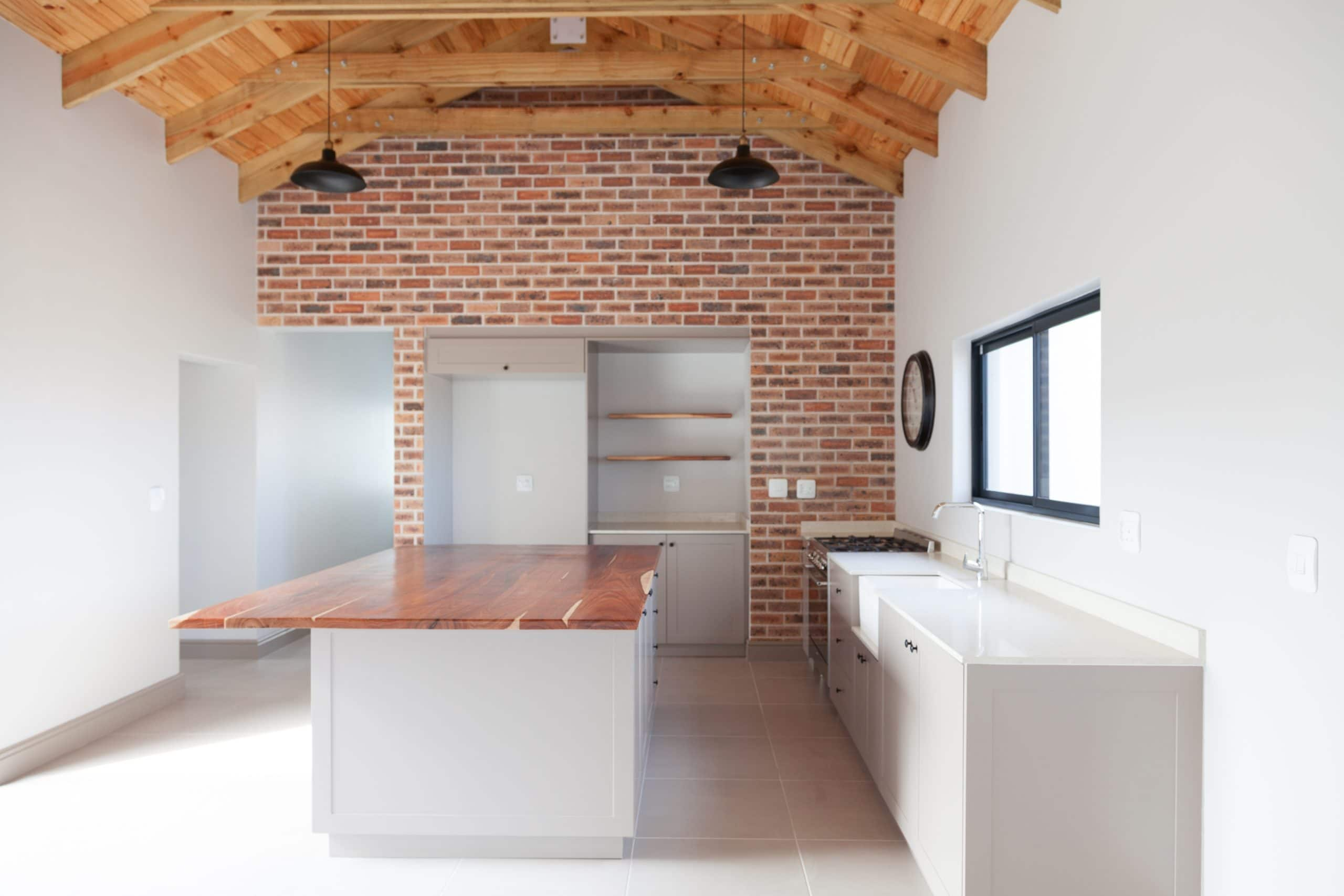 brown brick kitchen with dark black pendants and kiaat counter top