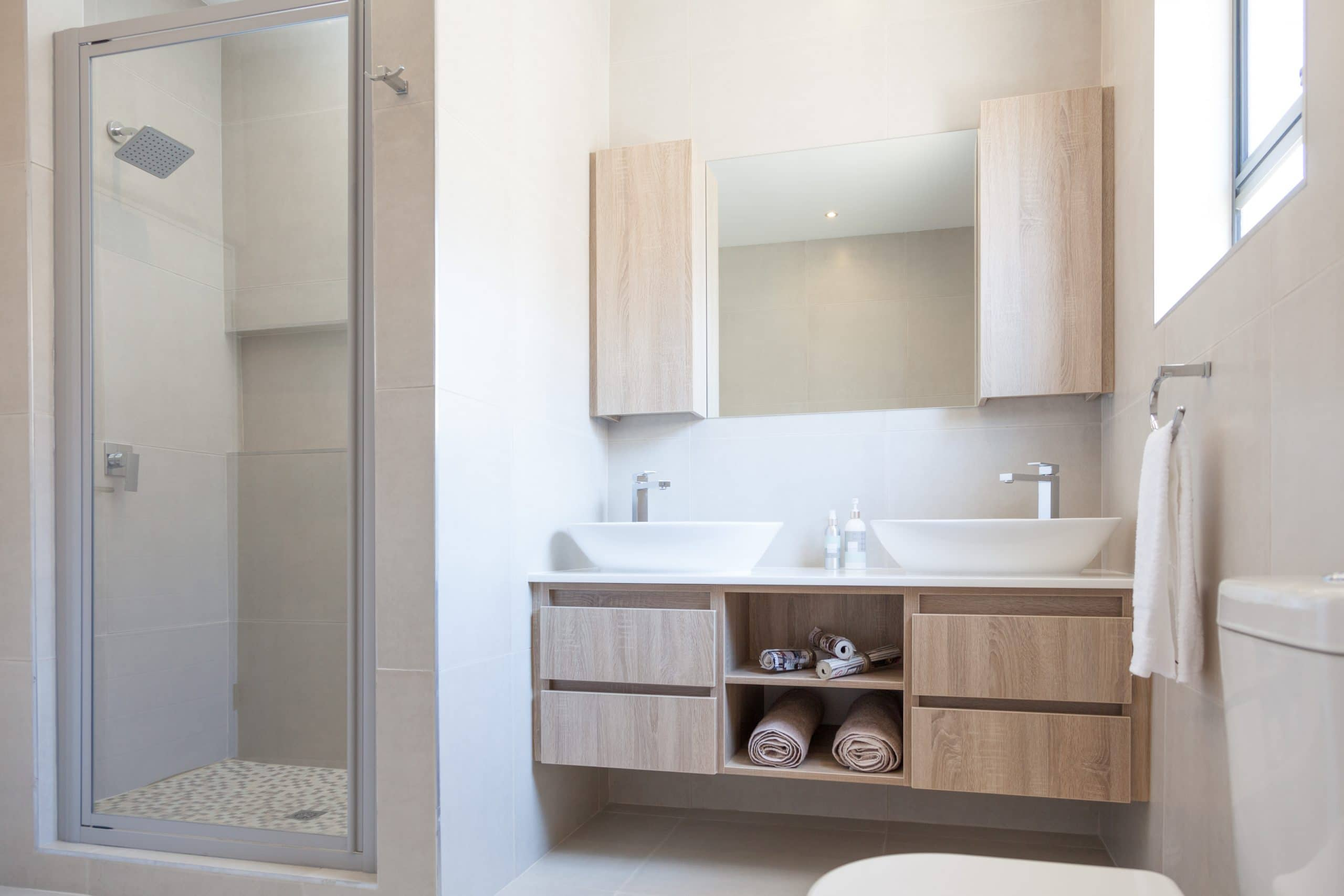 modern bathroom shower with double vanity basins and mirror