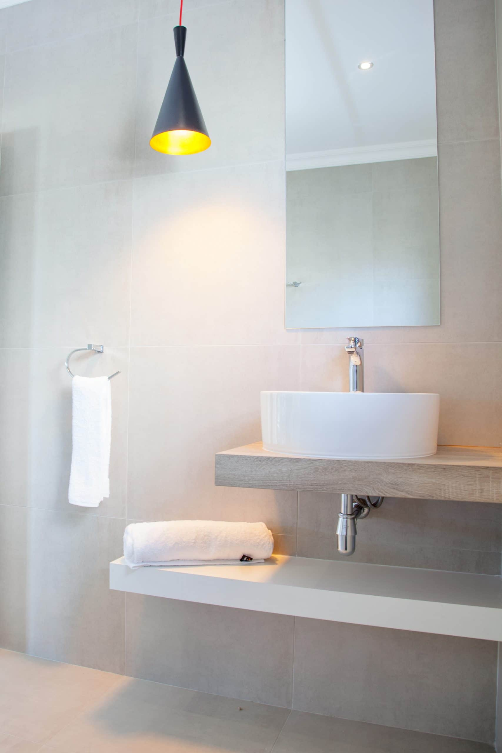 floating vanity with white towel and tiled bathroom walls