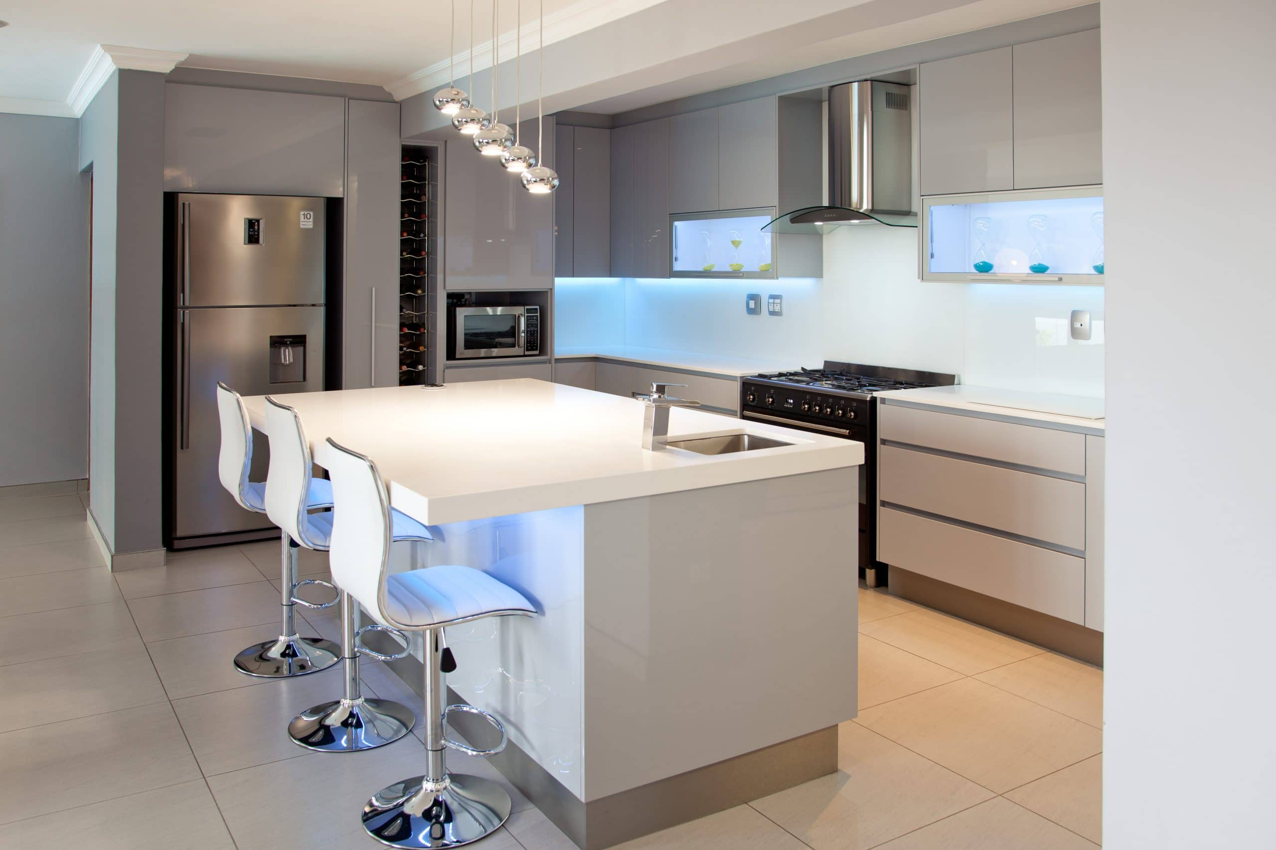 modern grey kitchen with black smeg oven and white quartz counter tops