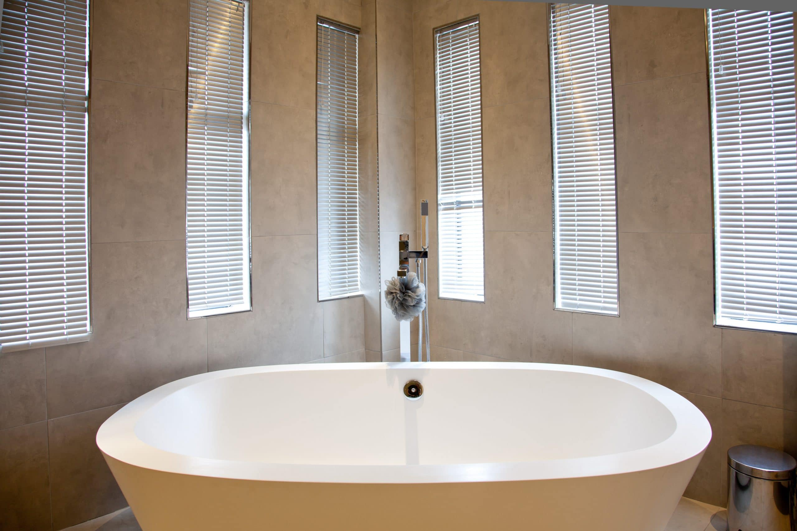 freestanding stone bath in corner of modern bathroom