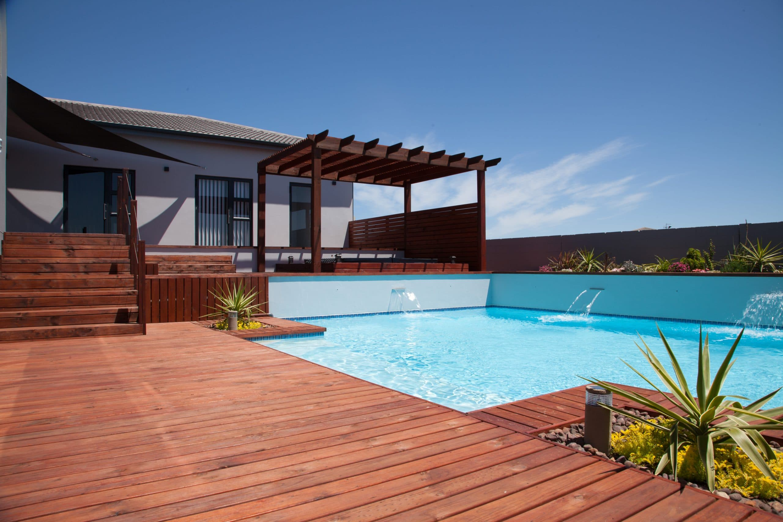 swimming pool with timber decking and pergola
