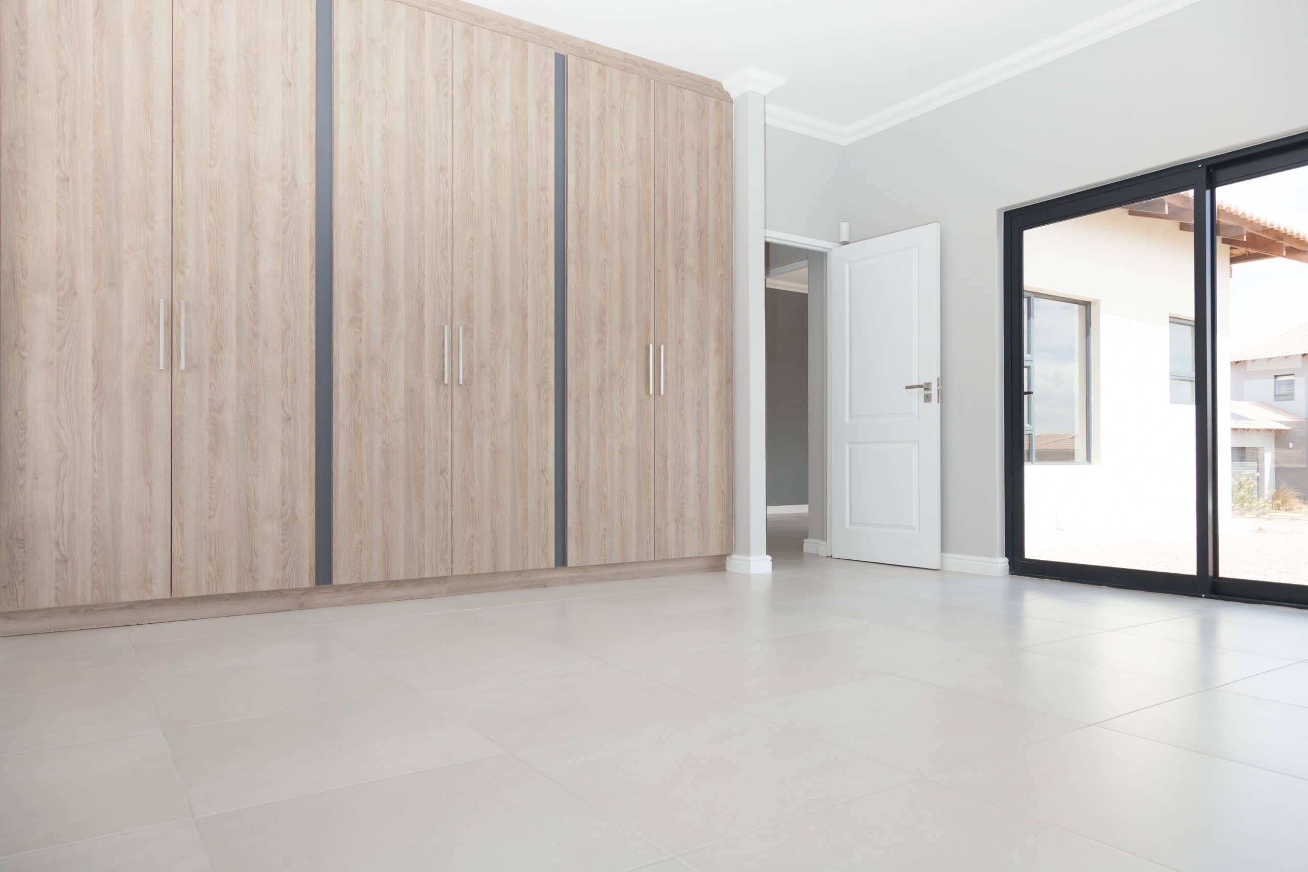 modern bedroom cupboards with stainless handles and cement flooring
