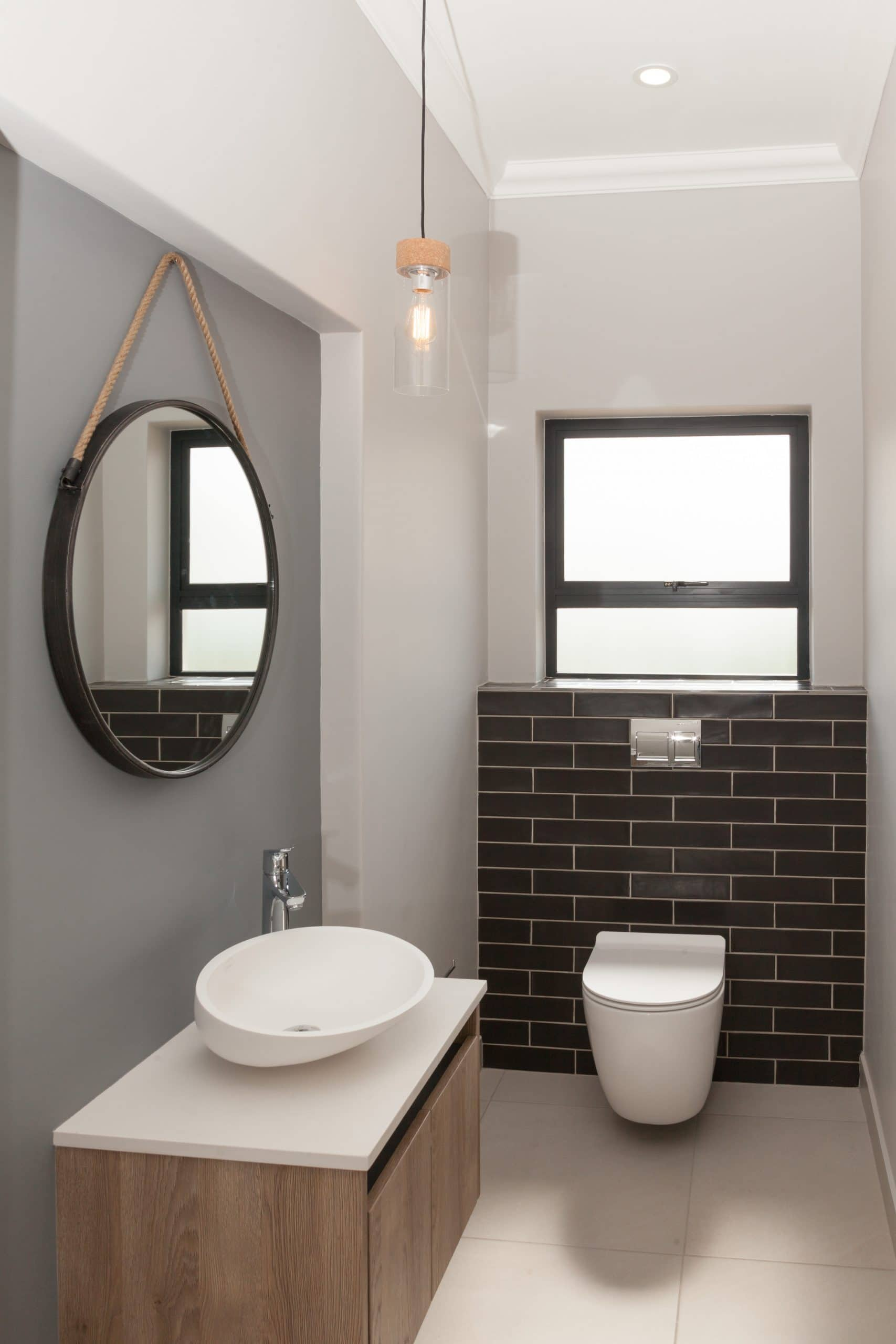 oval designer basin with hansgrohe basin mount taps grey slated subway tiles with hanging toilet
