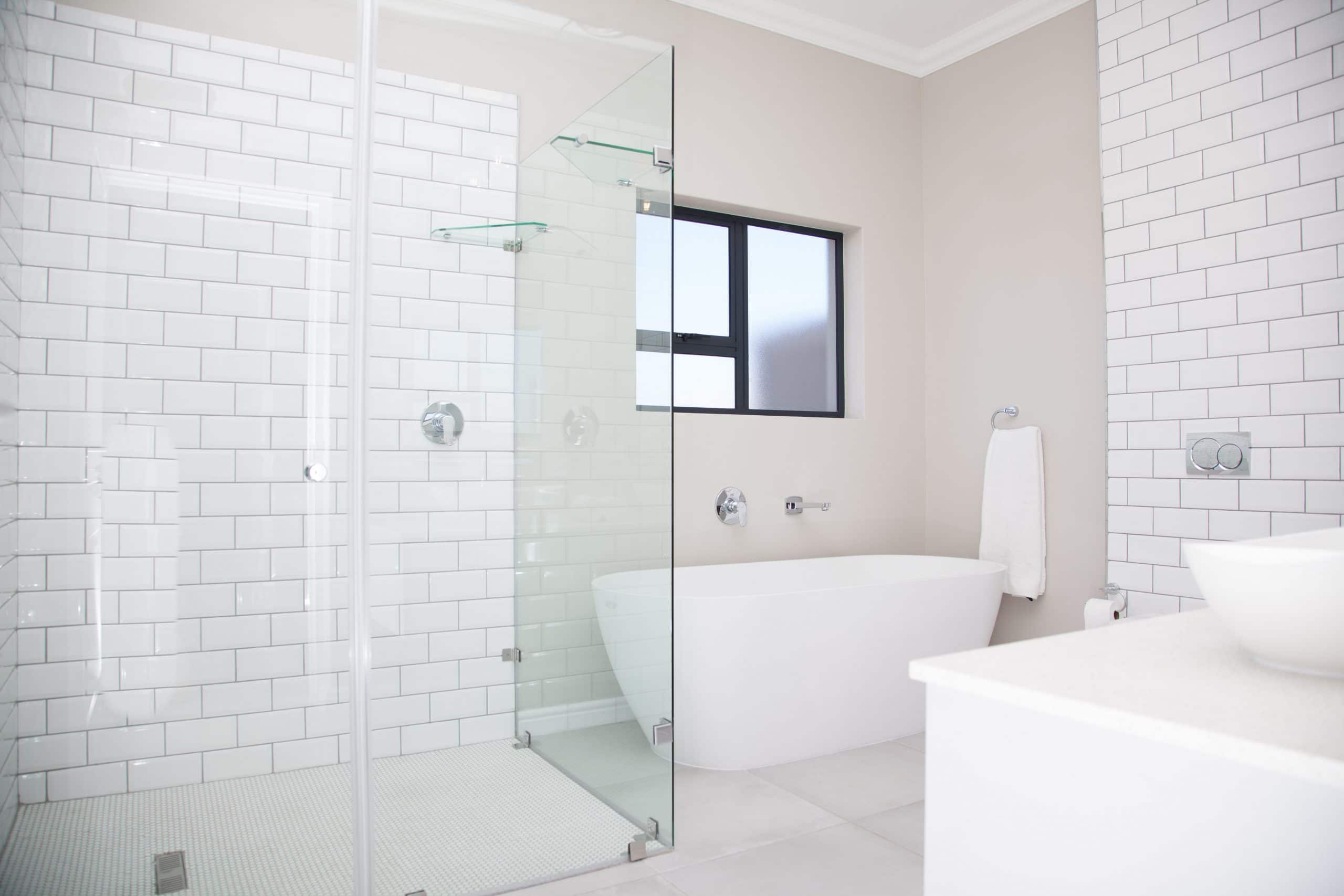 old school subway shower wall tiles with freestanding bath and white bathroom