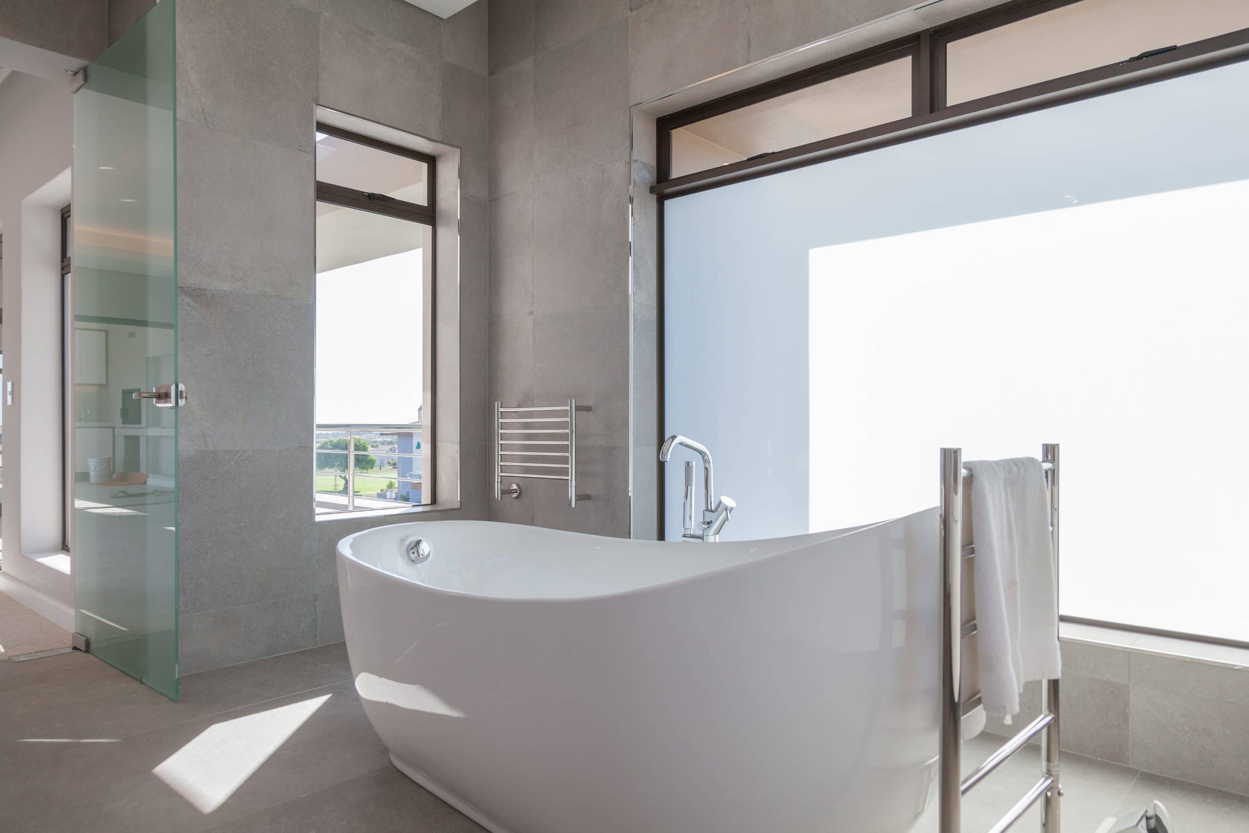 freestanding bath overlooking langebaan lagoon and glass bathroom door