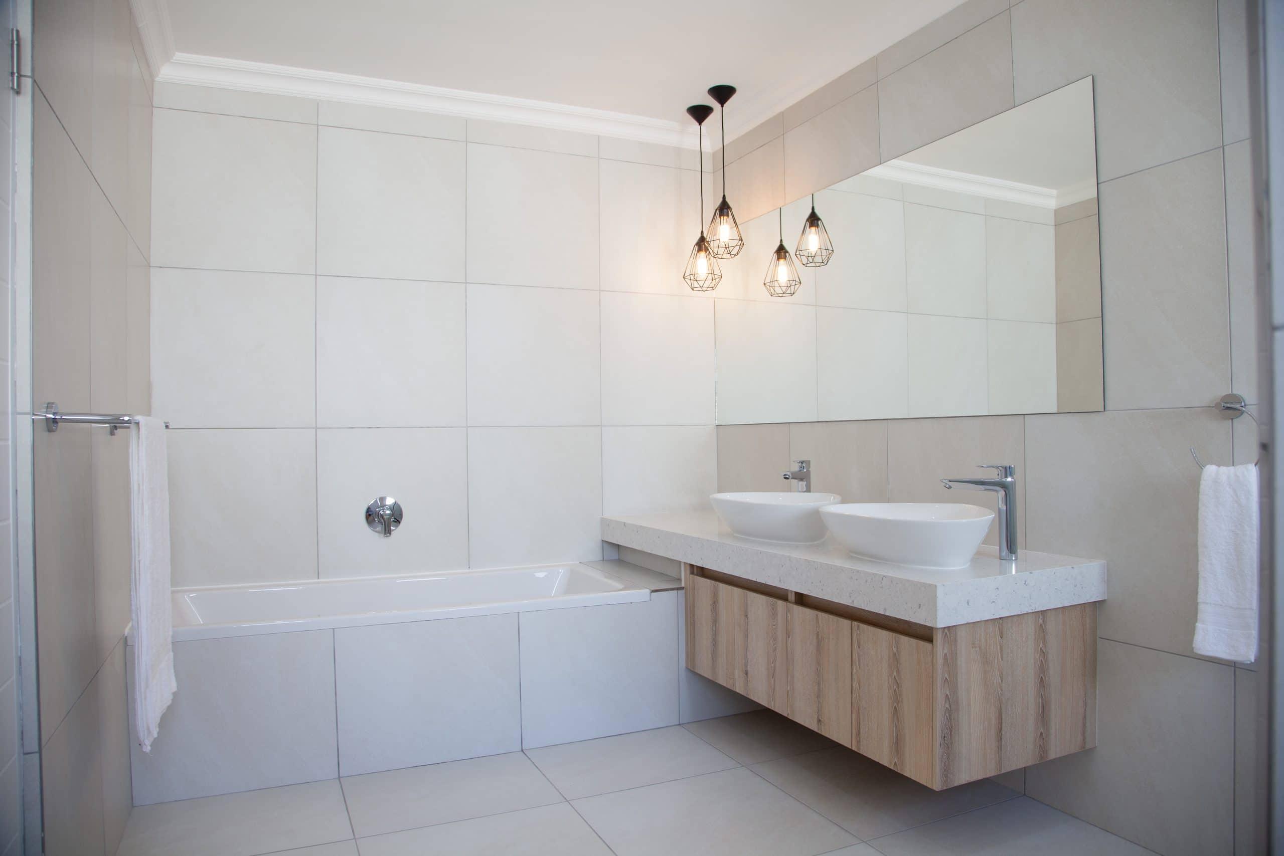 built-in bath with floating basin vanity and steel pendants bathroom