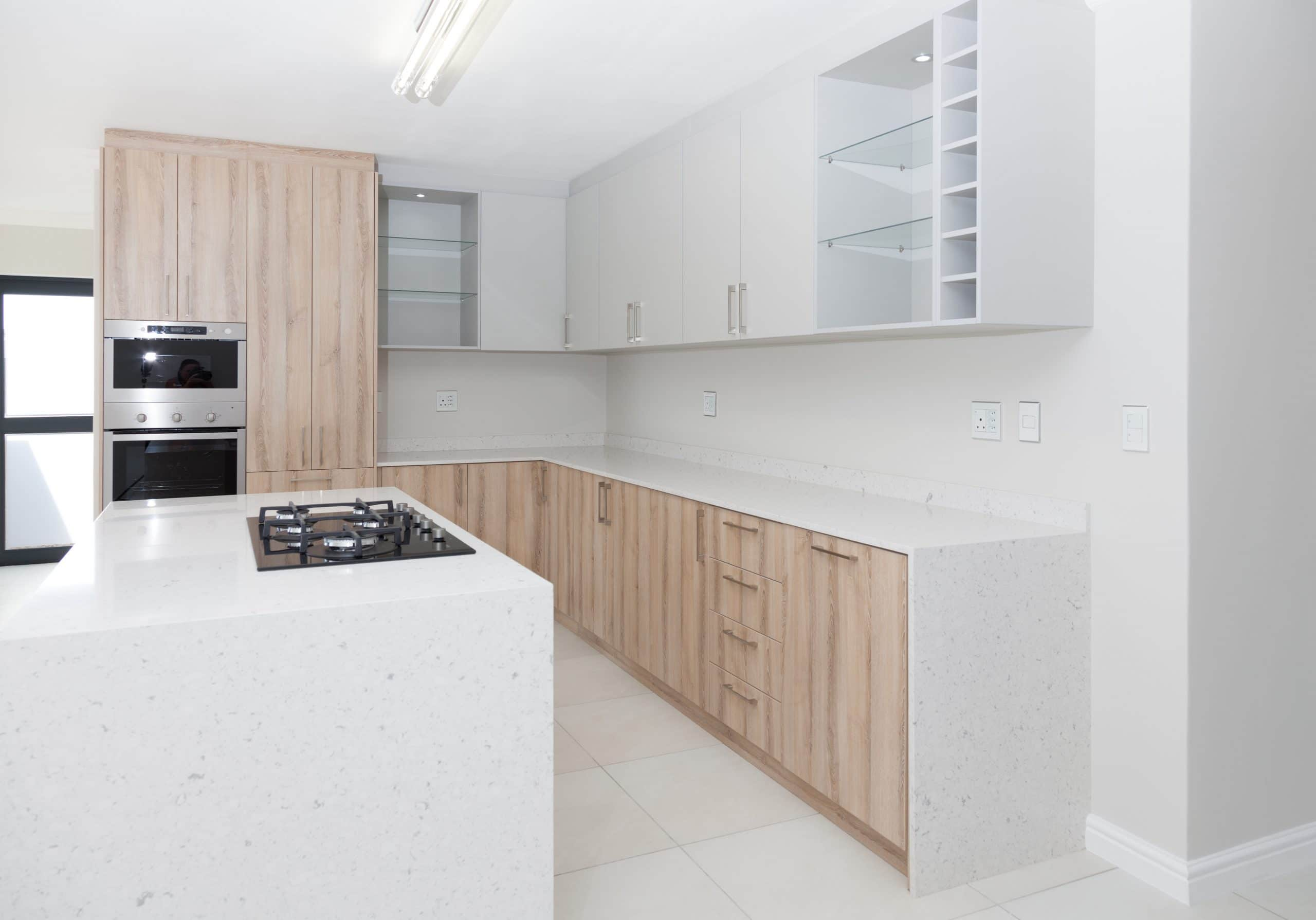 grey kitchen and eye level oven and glass shelves