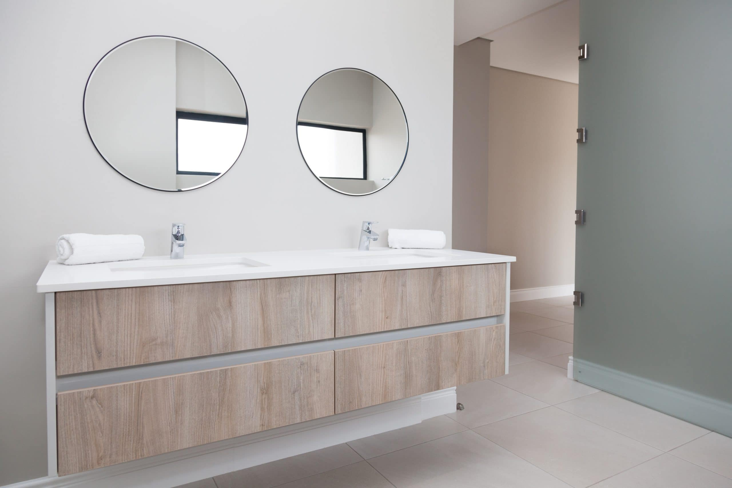 round bathroom mirrors with wooden vanity and glass bathroom door