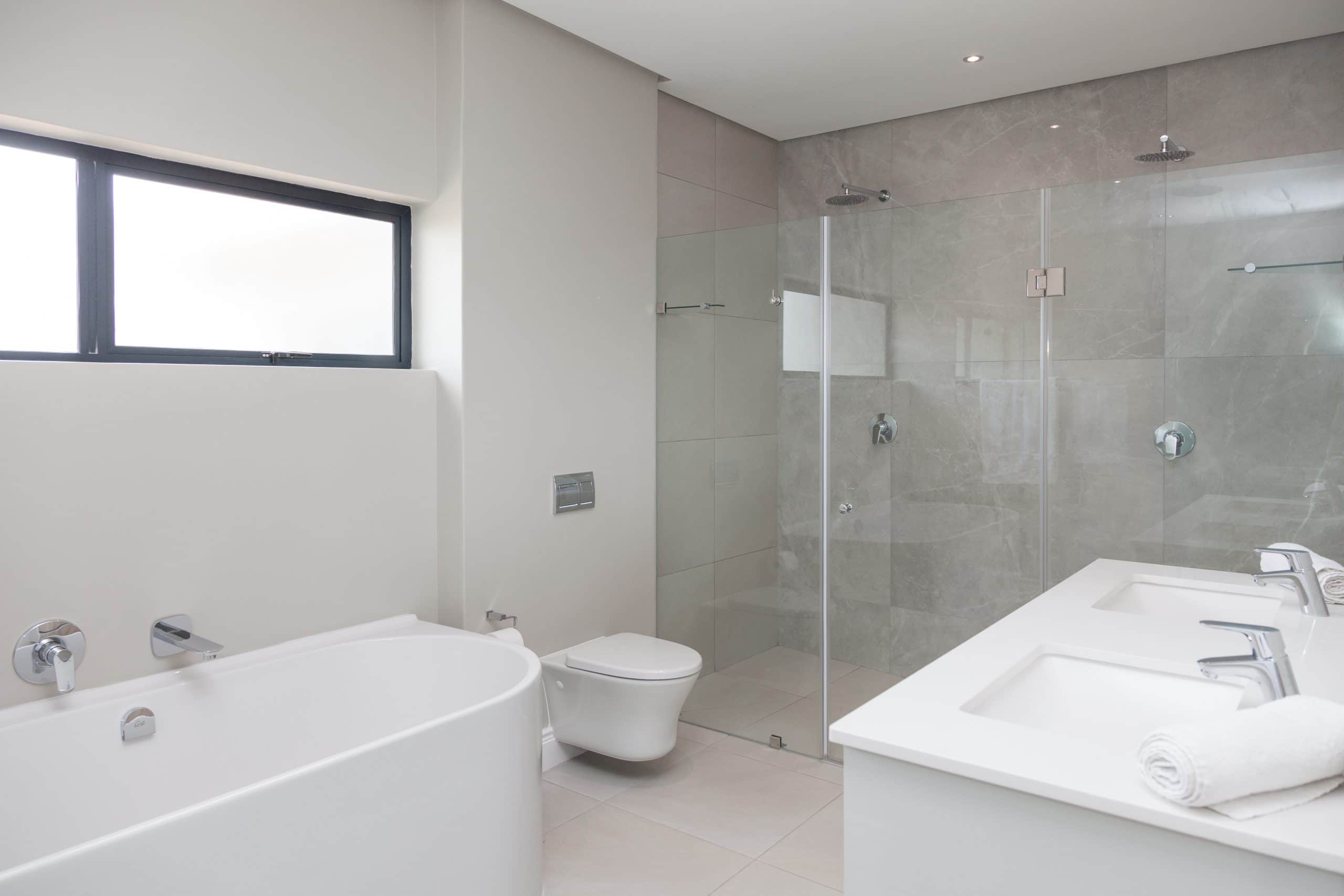 freestanding bath with frame less showers in langebaan country estate designed by carla cronje
