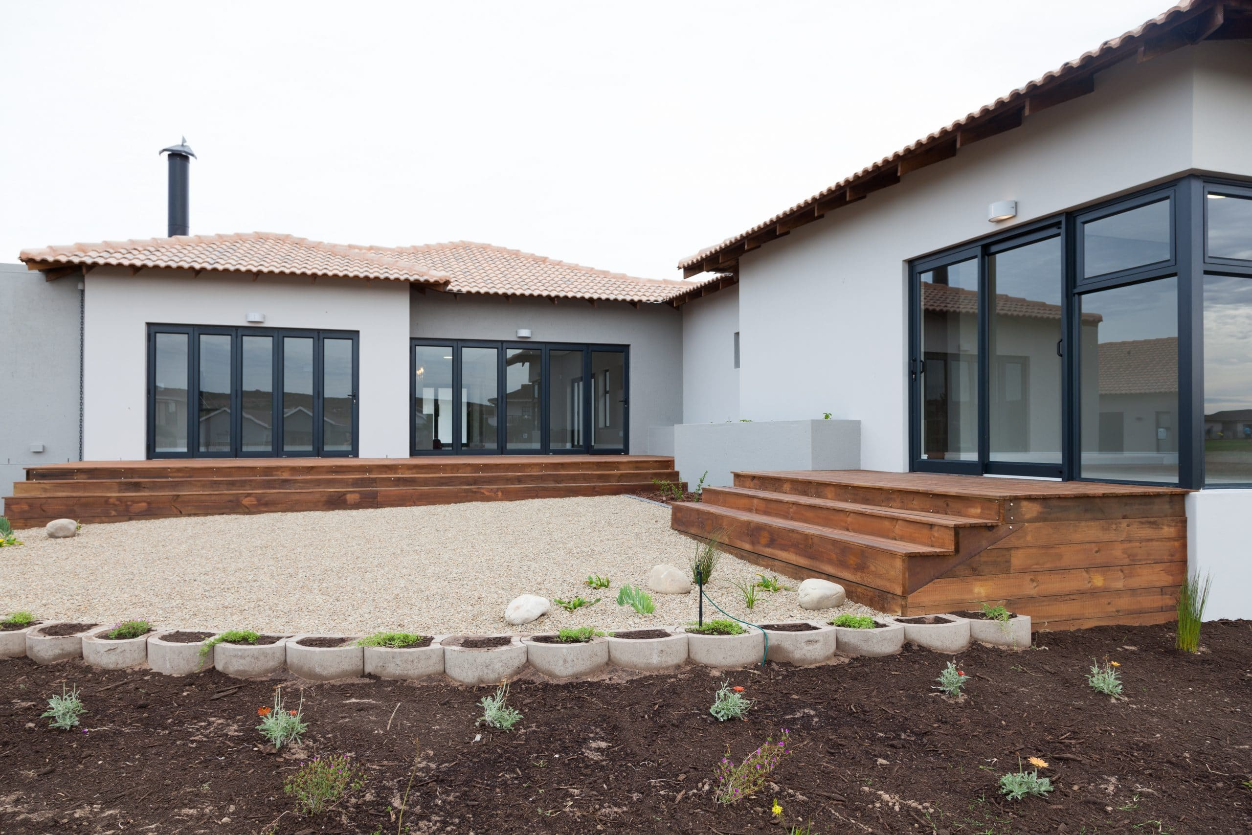 circle aggregate landscaped yard in langebaan country estate with wooden decking
