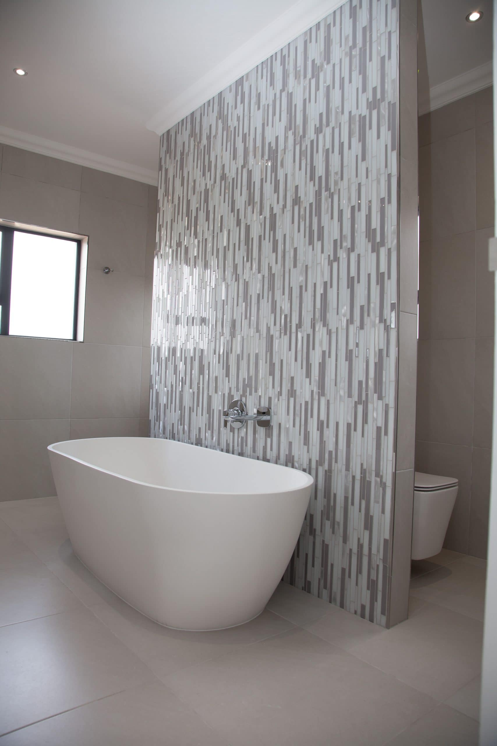 mosaic bathroom wall with freestanding bath