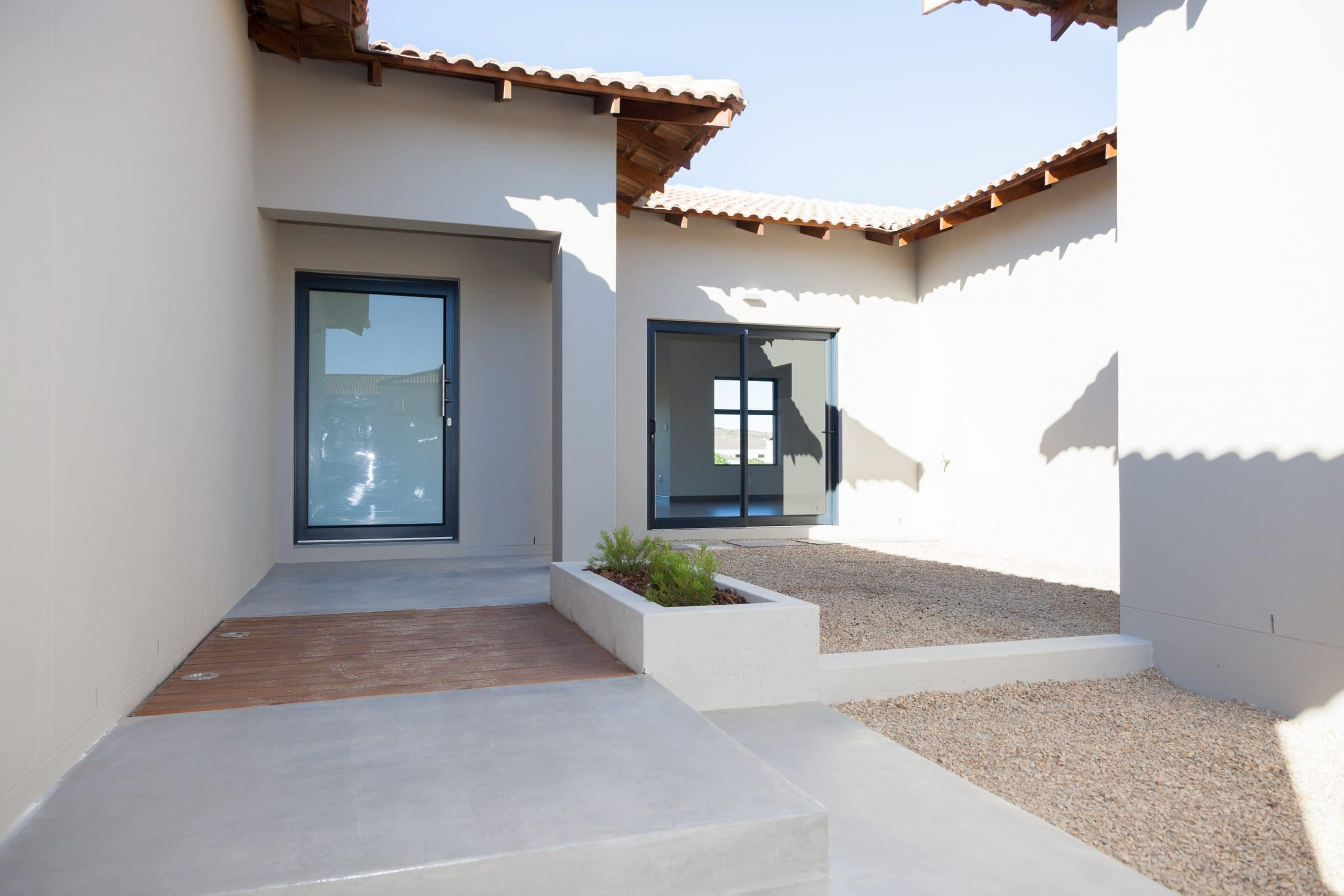 enclosed designer courtyard with flowerbox screed floor and wooden timber decking langebaan country estate