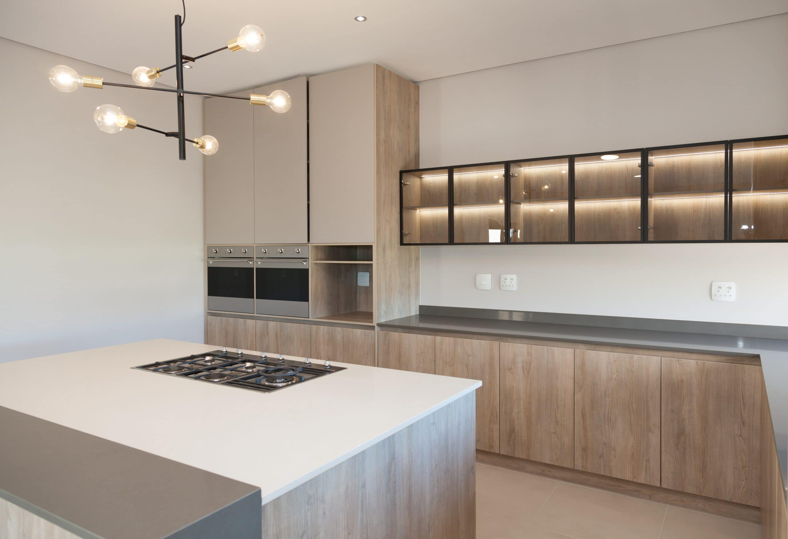 grey wood kitchen with glass doors and led lightning white counter tops smeg appliances