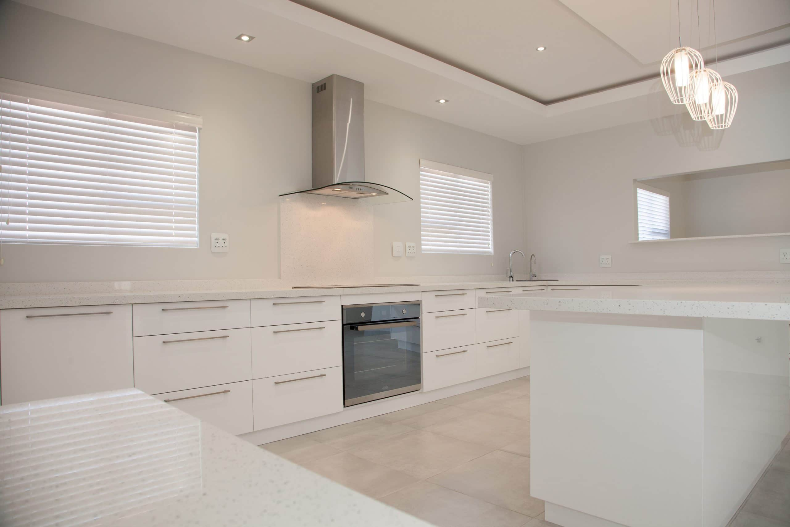 all white kitchen with glass cookerhood and built in oven langebaan