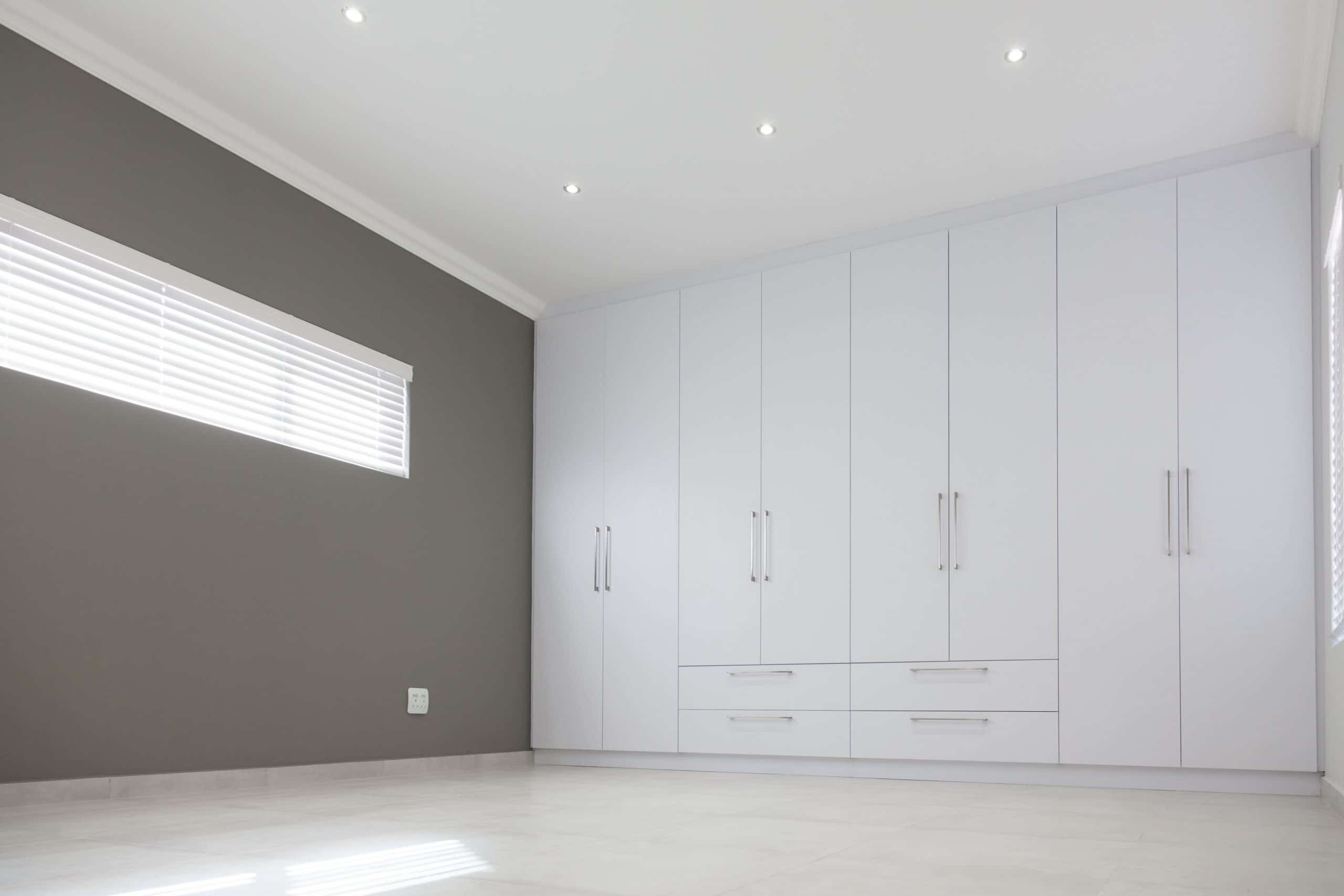 dark grey wall white bedroom cupboards