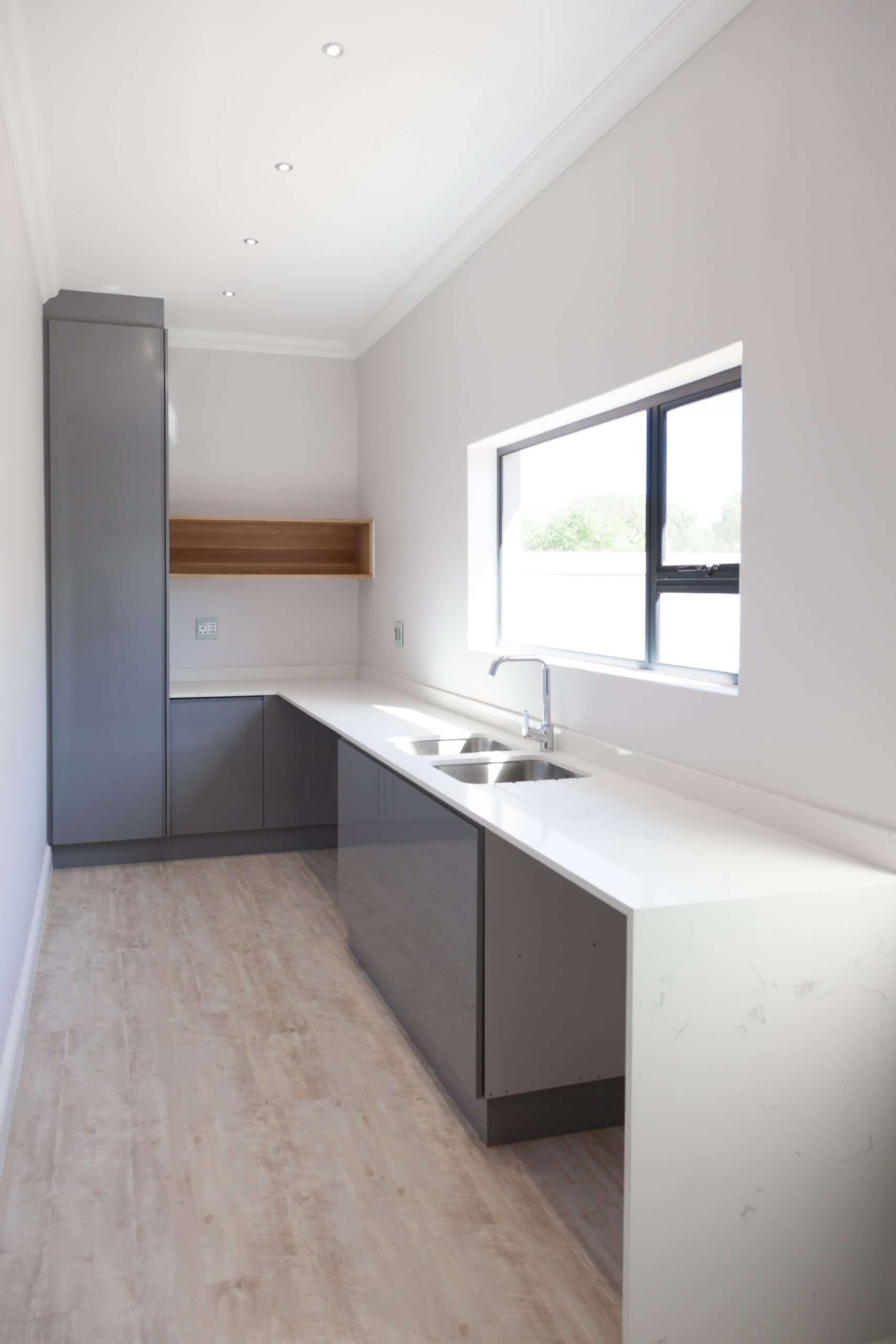 modern designed scullery grey spray cupboards and wooden flooring langebaan