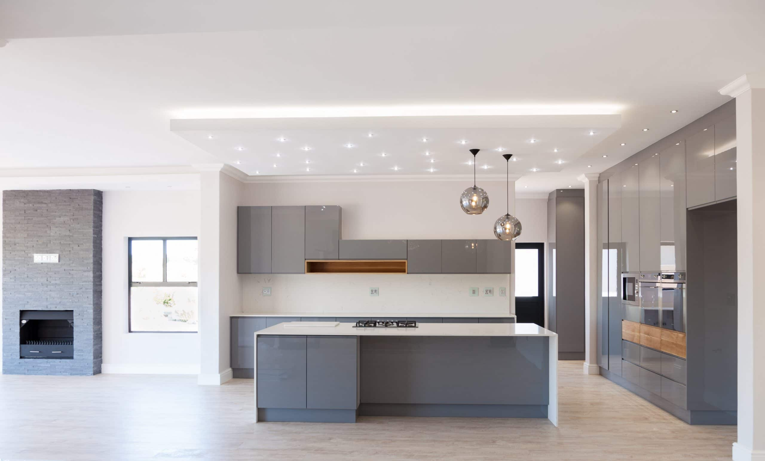 built in fireplace next to modern oak grey kitchen with led bulkhead ceiling and smeg appliances